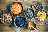 Various types of lentils in bowls on a rustic wooden surface