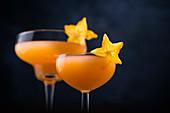 Peach Velvet Cocktail ( Sekt, Orangensaft, Pfirsichlikör und Grenadine), dekoriert mit Karambole