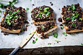 Tofu topped with black breadcrumbs, garnished with parsley and sesame seeds sliced (vegan)
