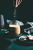 Braunen Zucker in Glas mit Milchkaffee streuen