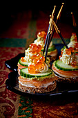 Black bread canapés with cucumber and salmon caviar