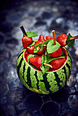 A watermelon filled with strawberry and mint skewers
