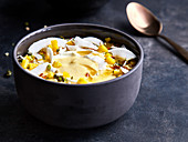 A smoothie bowl with mango and pistachio nuts