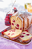 Raspberry loaf cake with icing and a berry salad
