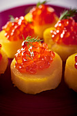 Baked potato slices with salmon caviar and dill, close-up