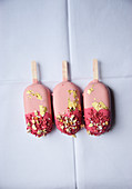 Drei rosa Popsicles mit Blattgold