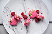 Raspberry macaroons with gold leaf and fresh raspberries