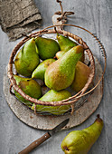 Pears in a wire basket with a peeler