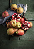Apples, pears and pomegranate in a bowl on a green wooden surface