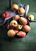 Apples and pears in a bowl on a green wooden surface