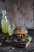 Vegan black bean burger served in whole grain bun with red cabbage, carrot and jalapeno