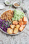 Vegan Buddha bowl - spicy roasted chickpeas and potatoes with cabbage slaw and guacamole