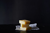 A stack of three slices of Emmental cheese