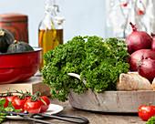 Petersilie und rote Zwiebel in einer Schale, Teller mit Tomaten