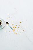 Croissantbrösel neben leergetrunkener Espressotasse