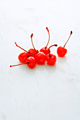 Glacé cherries on a white surface