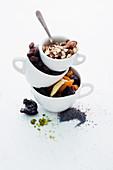 Stilleben mit Nüssen, Samen und Trockenfrüchten in Tassen