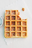 A waffle dusted with icing sugar with a bite taken out