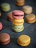 Bright fresh tasty macaron biscuits on grey board and dry fruits
