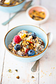 Vegan quinoa muesli with date and cashew cream, fruit and seeds