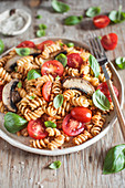 Fusilli pasta with pesto rosso, mushrooms, tomatoes and fresh basil