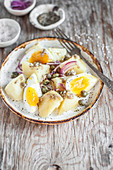 Potato salad with boiled egg, red onion and capers