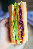 Vegan baguette sandwich with tofu, avocado, red cabbage and carrot habanero sauce