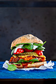 A burger with a pumpkin patty, cherry tomatoes and gherkins