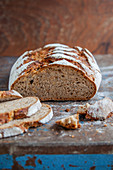 A long loaf of wholemeal sour dough bread, sliced