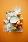 Ingredients for a peach dessert: flour, cream, eggs and peaches