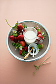 Strawberries with pepper and cream in a sieve