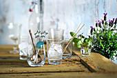 A bar arrangement with ice cubes, bar utensils, mint and lavender