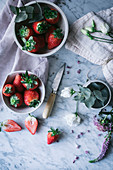 Bowls with ripe strawberries and beautiful flowers placed on white marble tabletop near knife