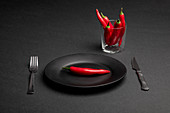 Fork and knife placed on black background near plate and cup with fresh chili peppers as representation of spicy dinner