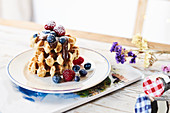 Plate with stack of golden waffles garnished with fresh berries and chocolate topping on table