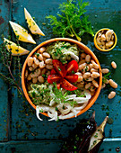 A bowl with cannellini beans, aubergine mousse, tomatoes, fennel and cashew nuts