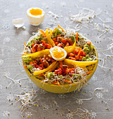 A bowl with sweet potatoes, peppers, guacamole, bean sprouts and egg