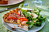 Vegetable tart and a green salad with young horseradish leaves and Parmesan cheese