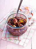 Homemade damson compote with orange zest in a preserving jar