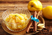 Preserved spiced quinces in a bowl with cinnamon