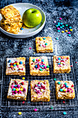 Apple pie cut into squares, decorated with multi-colored candies