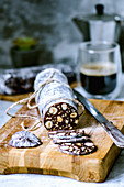Chocolate sausage with biscuits and hazelnuts, cut on a wooden board