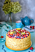 Honey cake decorated with berries, chocolate pieces and starfish stars