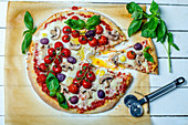 Homemade pizza with mushrooms, olives, quail eggs, cherry tomatoes and fresh basil