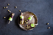 Avocado popsicles covered with dark chocolate and crushed pistachios
