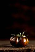 Kumato-Tomate mit Wassertropfen
