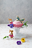 A cupcake with strawberry cream and butterfly biscuits, tufted pansies and forget-me-nots