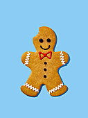 A gingerbread man with a bite taken out on a light blue surface