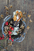 A napkin and cutlery in a basket decorated with rosehips, walnuts and beehnuts