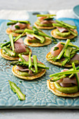 Blinis with Prague ham, green asparagus and avocado sour cream